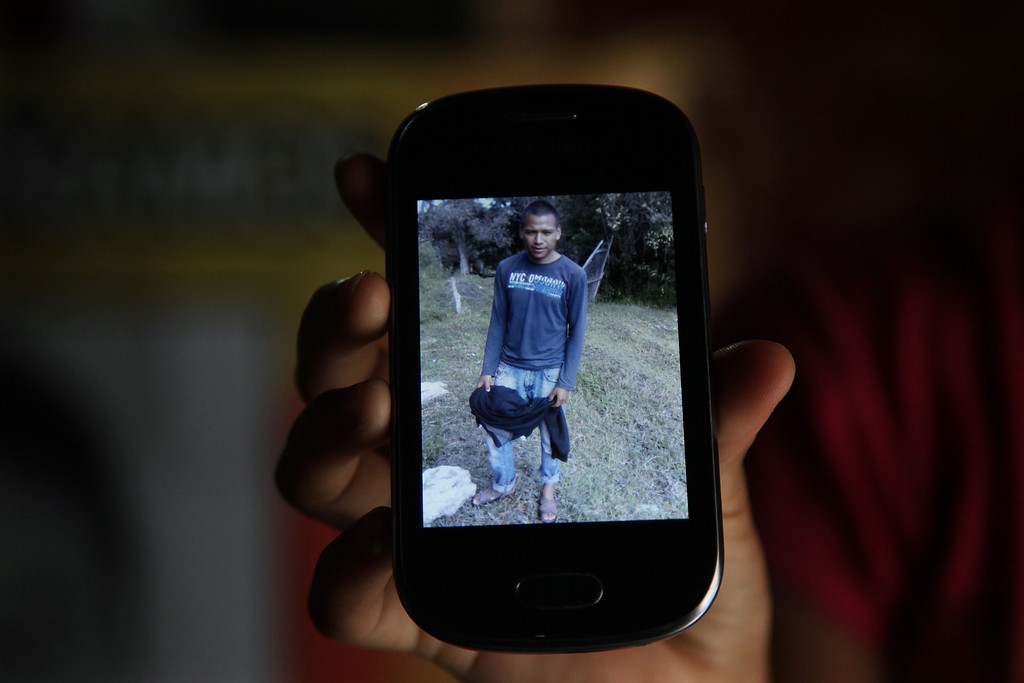 . In this Nov. 9, 2014 photo, the godmother of missing student Christian Rodriguez Telumbre, shows an image of Christian on her cellphone, in Tixtla, Mexico. Christian told his family he wanted a higher education to help support them. He had hoped to study agronomy at a university, but the family didn�t have the money. His only option was the tuition-free teacher�s college, known for Spartan living and radical politics dating back to the Mexican Revolution, the Rural Normal School of Ayotzinapa. (AP Photo/Marco Ugarte)