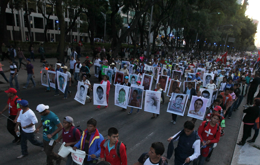 . Relatives holding posters with images of the missing students march in protest for the disappearance of 43 students in the state of Guerrero, in Mexico City, Wednesday, Nov. 5, 2014. Federal police detained yesterday Iguala Mayor Jose Luis Abarca and his wife, Maria de los Angeles Pineda, who are accused of ordering the Sept. 26 attacks on teachers\' college students that left six dead and 43 still missing. (AP Photo/Marco Ugarte)
