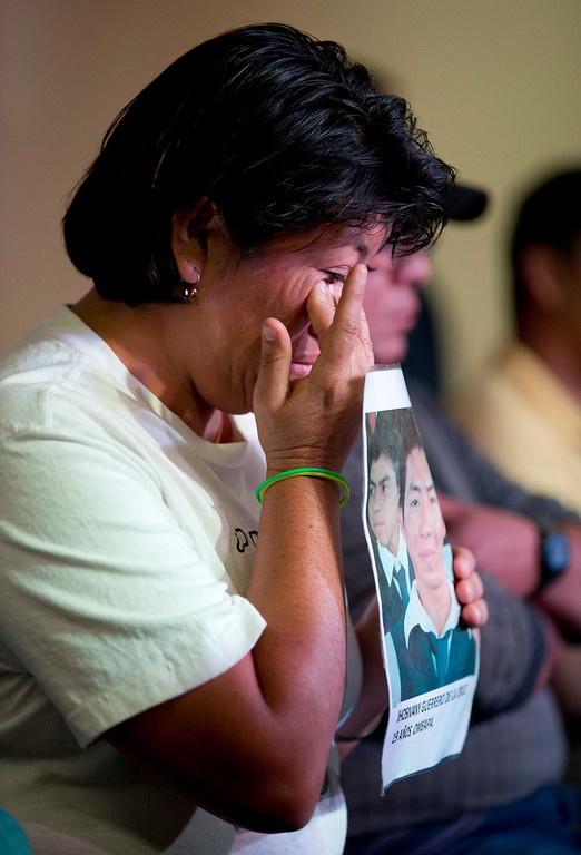 . A relative holding a picture of one of the missing students, wipes a tear from her face during a press conference by the family members of the missing, in Mexico, City, Tuesday Jan. 27, 2015. Mexican attorney general Jesus Murillo Karam said that investigators are now certain that 43 college students missing since September were killed and incinerated after they were seized by police in southern Guerrero state. It was the first time Murillo Karam said definitely that all were dead, even though Mexican authorities have DNA identification for only one student and a declaration from a laboratory in Innsbruck, Austria, that it appears impossible to identify the others. (AP Photo/Eduardo Verdugo)