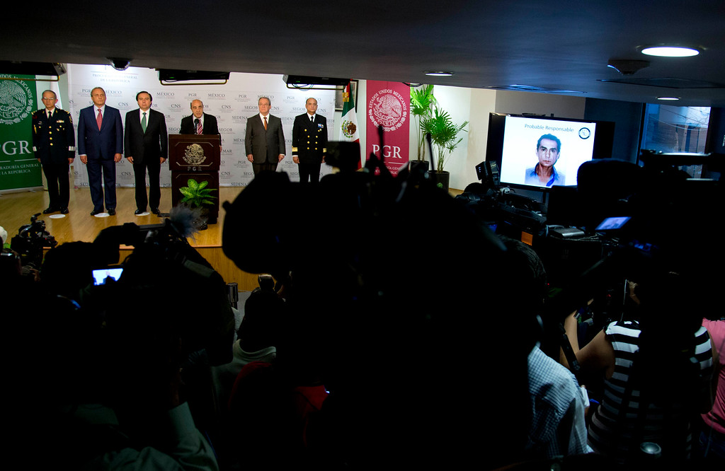 . Mexico\'s Attorney General, Jesus Murillo Karam, center, shows a tv screen with the image of the former mayor of the southern Mexican city of Iguala Jose Luis Abarca, during a news conference in Mexico City, Tuesday Nov. 4, 2014. Karam gave details about the capture of Mexico\'s most-wanted couple, accused of running their town as a drug fiefdom and ordering an attack that killed six and left 43 college students missing, were caught Tuesday in a rough-and-tumble neighborhood of Mexico City where they were hiding. Authorities have uncovered mass graves and the remains of 38 people, but none has been identified as the missing students. (AP Photo/Eduardo Verdugo)