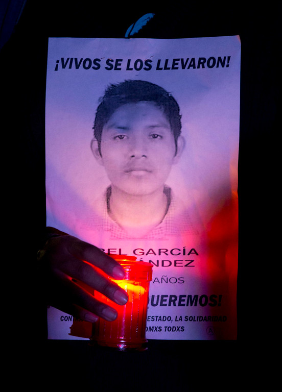 """. A woman marches with a candle and a leaflet with the image of one a missing students during a protest against the disappearance of 43 students from the Isidro Burgos rural teachers college, in Mexico City, Wednesday, Oct. 22, 2014. The leaflet reads in Spanish \""""They took them alive!\"""" Tens of thousands marched in Mexico City\'s main avenue demanding the return of the missing students. The Mexican government says it still does not know what happened to the young people after they were rounded up by local police in Iguala, a town in southern Mexico, and allegedly handed over to gunmen from a drug cartel Sept. 26, even though authorities have arrested 50 people allegedly involved. They include police officers and alleged members of the Guerreros Unidos cartel. (AP Photo/Eduardo Verdugo)"""