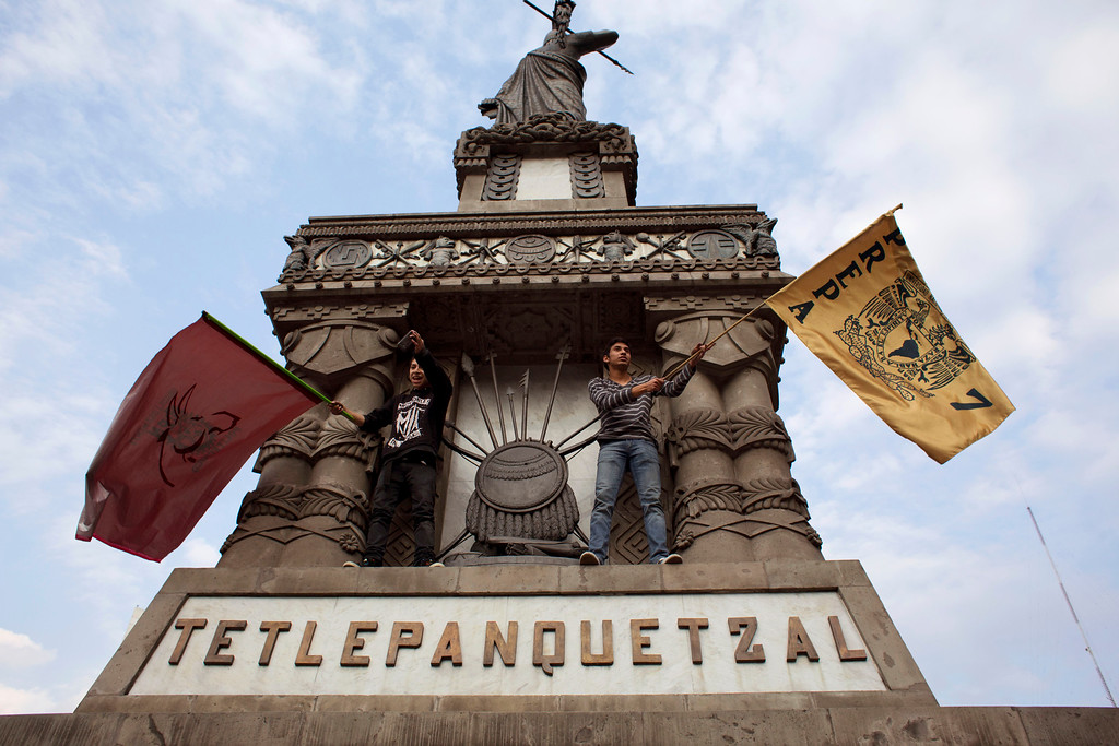 . University students wave their school flags from a monument during a protest marking four months since the disappearance of 43 students from a rural teachers\' college, in Mexico City, Monday, Jan. 26, 2015. Prosecutors have said police kidnapped the students on Sept. 26 in the southern state of Guerrero and handed them over to drug gang members, who killed them and burned the bodies. Protestors say the government has failed to provide sufficient proof to clear up doubts over the students\' fate. (AP Photo/Rebecca Blackwell)