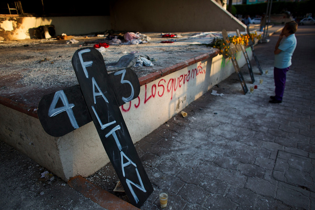 """. A local resident pauses to contemplate crosses set to remember 43 missing students, in front of the burnt town hall, in Iguala, Mexico, Tuesday, Oct. 28, 2014. The cross at left reads in Spanish \""""43 are missing.\"""" Forensic experts combed a gully in southern Mexico on Tuesday for the remains of students, as frustration mounted among relatives of both the disappeared and the detained for the lack of answers more than a month into the investigation. (AP Photo/Rebecca Blackwell)"""