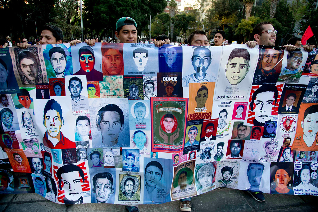 . Demonstrators march holding images of missing students in protest for the disappearance of 43 students in the state of Guerrero, in Mexico City, Wednesday, Nov. 5, 2014. Federal police detained yesterday Iguala Mayor Jose Luis Abarca and his wife, Maria de los Angeles Pineda, who are accused of ordering the Sept. 26 attacks on teachers\' college students that left six dead and 43 still missing.  (AP Photo/Eduardo Verdugo)