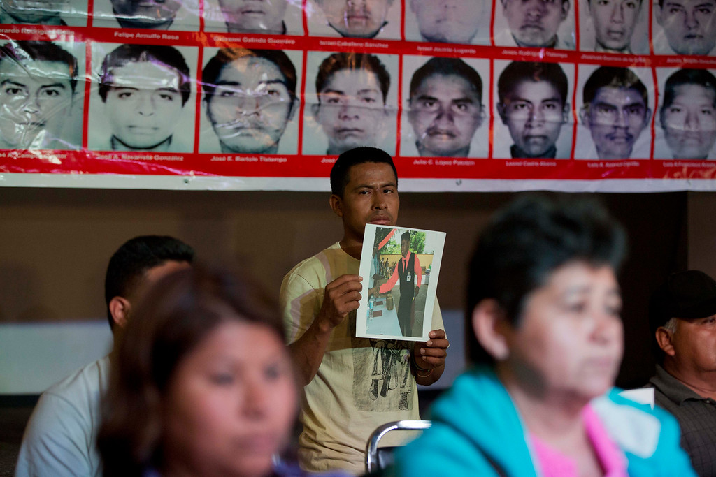 . A relative holds a picture of one of the missing students in front of a banner with the photos of the missing during a press conference by family members of the disappeared students, in Mexico, City, Tuesday Jan. 27, 2015. Mexican attorney general Jesus Murillo Karam said that investigators are now certain that 43 college students missing since September were killed and incinerated after they were seized by police in southern Guerrero state. It was the first time Murillo Karam said definitely that all were dead, even though Mexican authorities have DNA identification for only one student and a declaration from a laboratory in Innsbruck, Austria, that it appears impossible to identify the others. (AP Photo/Eduardo Verdugo)