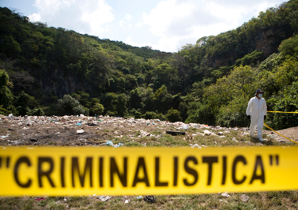 . A forensic examiner walks along a garbage-strewn hillside above a ravine where examiners are searching for human remains in densely forested mountains outside Cocula, Guerrero state, Mexico, Tuesday, Oct. 28, 2014. Suspects arrested this week told prosecutors that many of the 43 students who disappeared Sept. 26 from the town of Iguala had been held near this location. (AP Photo/Rebecca Blackwell, Pool)
