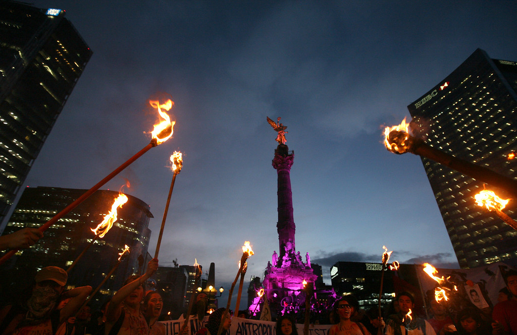 . Demonstrators hold torches in front of the Mexican Independence Monument during a march in protest for the disappearance of 43 students from the Isidro Burgos rural teachers college, in Mexico City, Wednesday, Oct. 22, 2014. Tens of thousands marched in Mexico City\'s main avenue demanding the return of the missing students. The Mexican government says it still does not know what happened to the young people after they were rounded up by local police in Iguala, a town in southern Mexico, and allegedly handed over to gunmen from a drug cartel Sept. 26, even though authorities have arrested 50 people allegedly involved. They include police officers and alleged members of the Guerreros Unidos cartel. (AP Photo/Marco Ugarte)