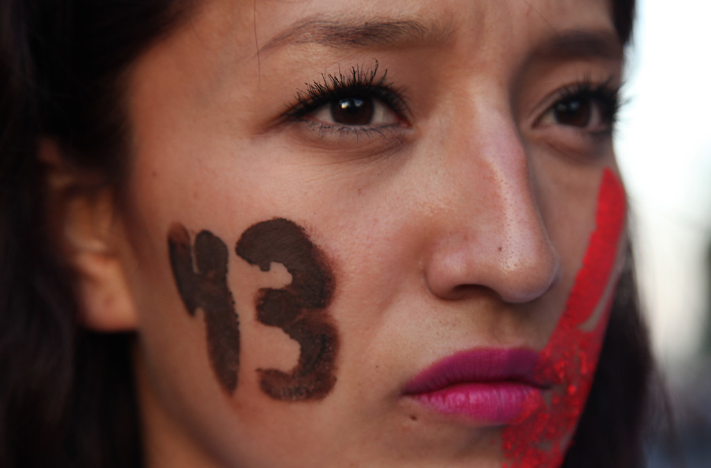 . A female demonstrator with the number 43 painted on her face marches in protest for the disappearance of 43 students in the state of Guerrero, in Mexico City, Wednesday, Nov. 5, 2014. Federal police detained yesterday Iguala Mayor Jose Luis Abarca and his wife, Maria de los Angeles Pineda, who are accused of ordering the Sept. 26 attacks on teachers\' college students that left six dead and 43 still missing. (AP Photo/Marco Ugarte)
