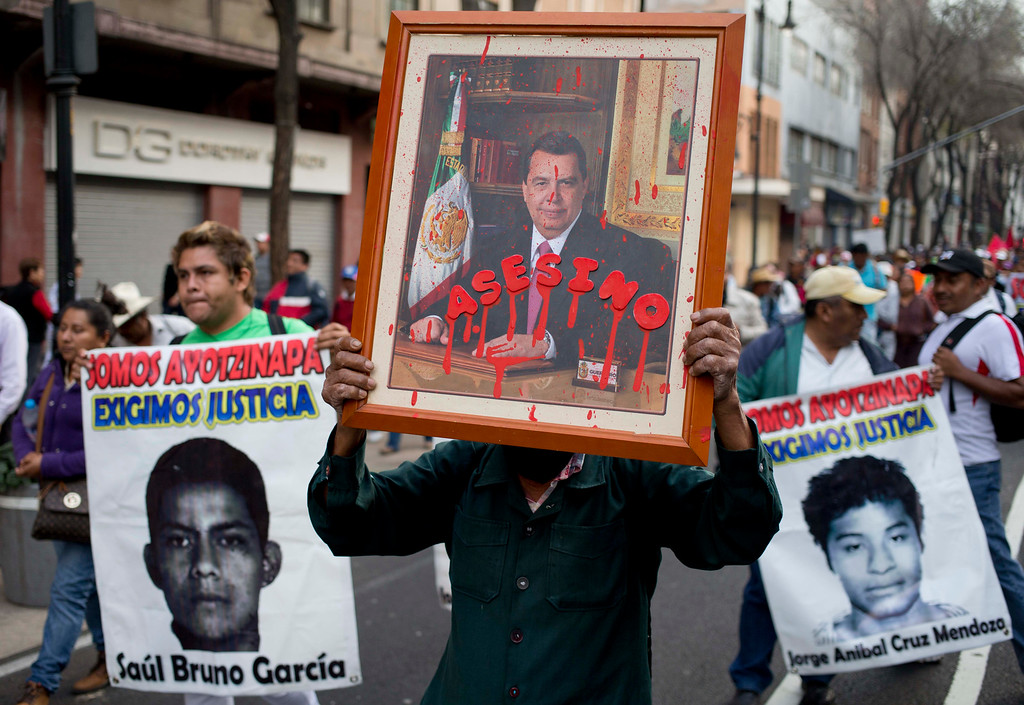 """. A protestor carries a defaced portrait of the former governor of Guerrero state, Angel Aguirre, covered by the word in Spanish \""""Assassin\"""" during a march marking the fourth month since the disappearance of 43 students from a rural teachers\' college, in Mexico City, Monday, Jan. 26, 2015. Prosecutors have said police kidnapped the students on Sept. 26 in the southern state of Guerrero and handed them over to drug gang members, who killed them and burned the bodies. Protesters said Monday the government has failed to clear up doubts. (AP Photo/Eduardo Verdugo)"""
