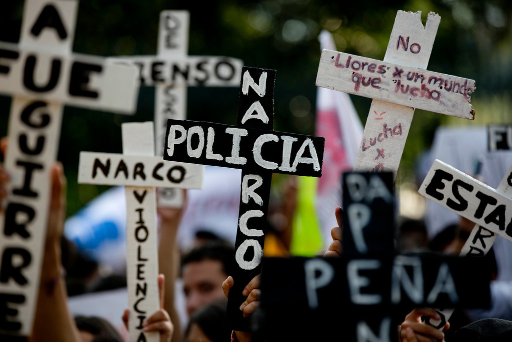 """. Demonstrators march with crosses with writing that reads in Spanish \""""Narco Cops\"""" in protest for the disappearance of 43 students in the state of Guerrero, in Mexico City, Wednesday, Nov. 5, 2014. Federal police detained yesterday Iguala Mayor Jose Luis Abarca and his wife, Maria de los Angeles Pineda, who are accused of ordering the Sept. 26 attacks on teachers\' college students that left six dead and 43 still missing.  (AP Photo/Eduardo Verdugo)"""