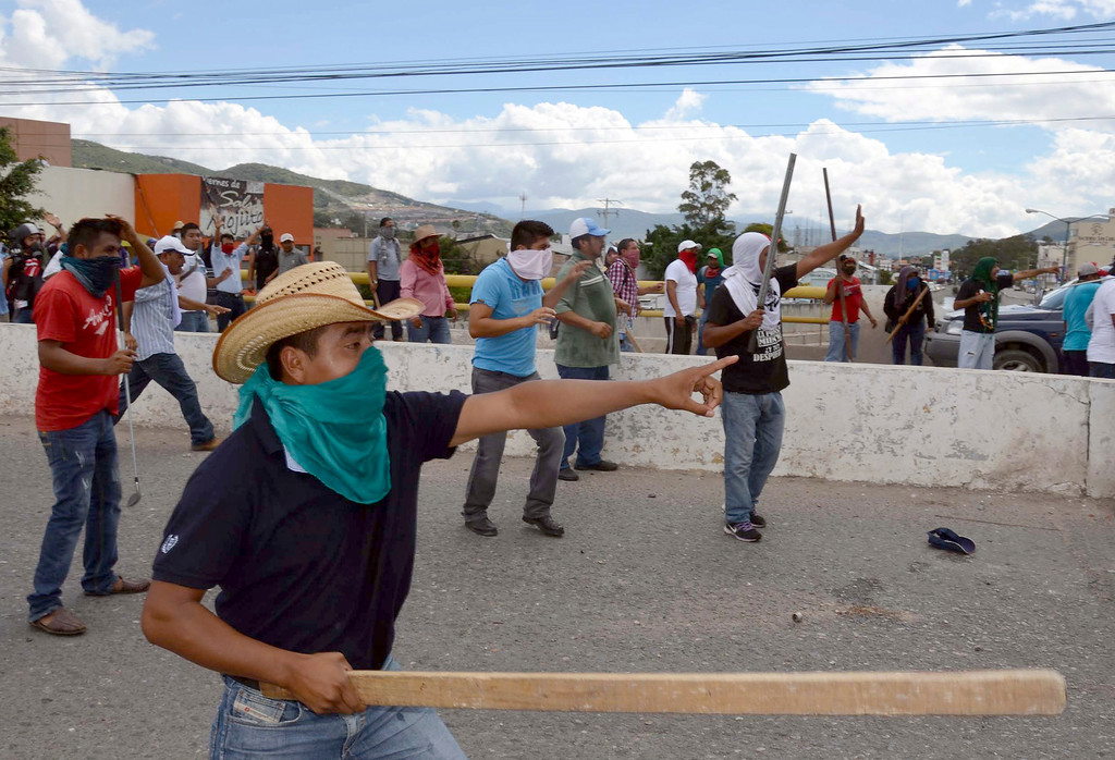 . Masked teachers carry clubs during a clash with riot police in Chilpancingo, Mexico, Tuesday, Nov. 11, 2014. Supporters of the missing 43 college rural students, refusing to believe they are dead, have kept up the protests that have blocked major highways and set government buildings ablaze in recent weeks. The students disappeared at the hands of a city police force on Sept. 26 in the town of Iguala. (AP Photo/Alejandrino Gonzalez)