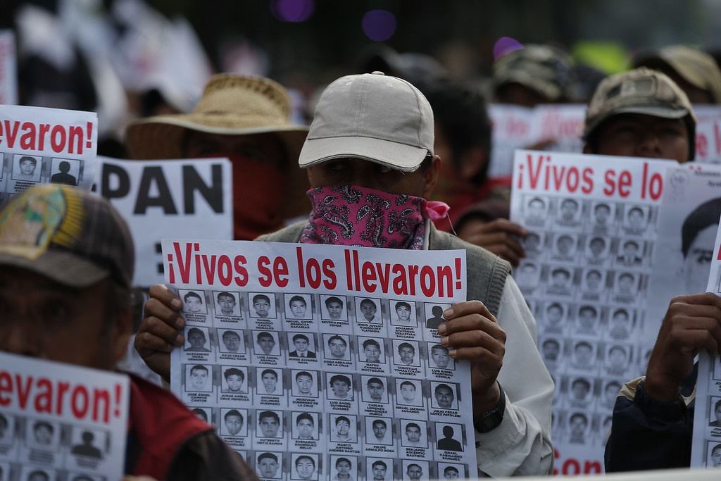 """. People march holding posters with the images of missing students that read in Spanish \""""They took them alive,\"""" to protest the disappearance of 43 students from the Isidro Burgos rural teachers college in  Mexico City, Wednesday, Oct. 22, 2014. Tens of thousands marched in Mexico City\'s main avenue demanding the return of the missing students. The Mexican government says it still does not know what happened to the young people after they were rounded up by local police in Iguala, a town in southern Mexico, and allegedly handed over to gunmen from a drug cartel Sept. 26, even though authorities have arrested 50 people allegedly involved. They include police officers and alleged members of the Guerreros Unidos cartel. (AP Photo/Eduardo Verdugo)"""