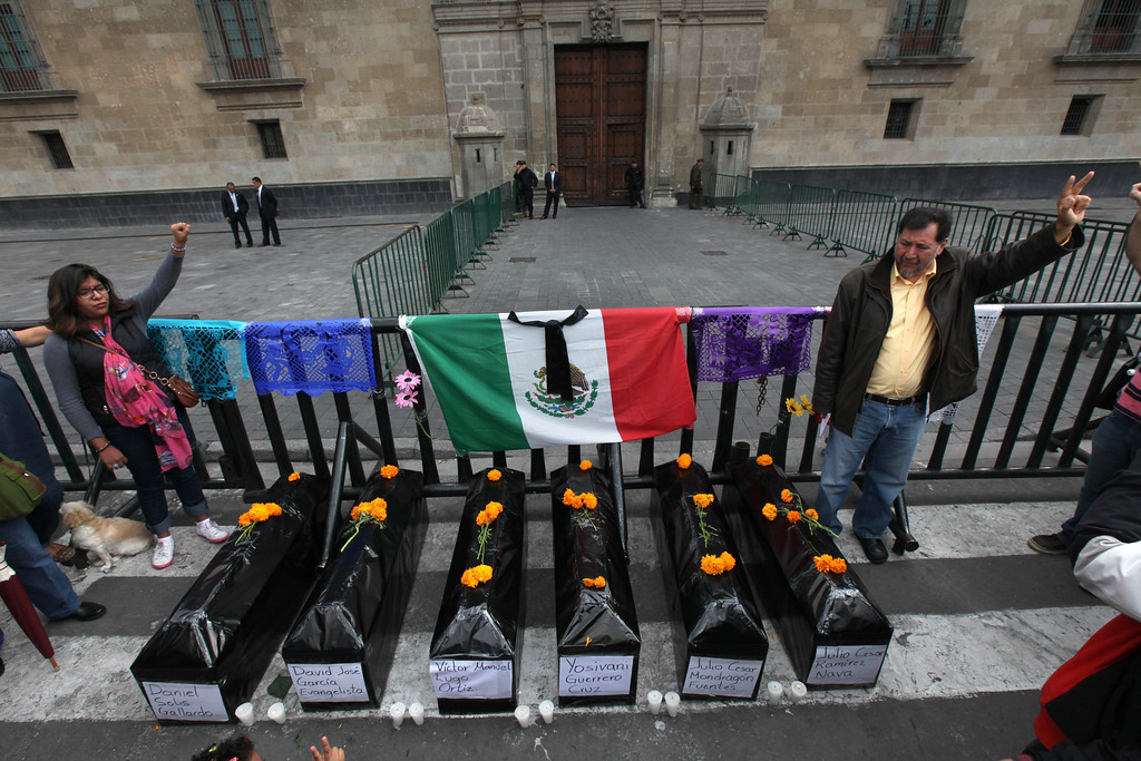 . Protesters stand next to six mock coffins, representing those who died in a police attack in Guerrero state, as they demonstrate outside the National Palace in Mexico City, Saturday, Nov. 1, 2014. Relatives of the missing have grown increasingly frustrated at the pace of the investigation of the Sept. 26 police attack in the city of Iguala, that left six dead and 43 missing students. The missing were apparently handed over to a drug gang by city police. (AP Photo/Marco Ugarte)