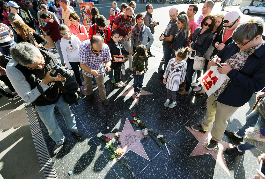 ". Passersby look at and photograph an impromptu memorial created on a blank Hollywood Walk of Fame star by fans of late actress and author Carrie Fisher, who does not have an official star on the world-famous promenade, in Los Angeles Wednesday, Dec. 28, 2016. Paste-on letters spell out her name and the phrase ""May the force be with you always.\"" (AP Photo/Reed Saxon)"