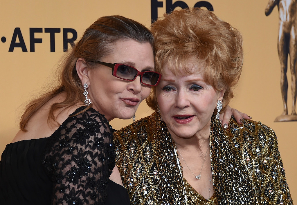 . Debbie Reynolds, recipient of the Screen Actors Guild Life Achievement Award, and Carrie Fisher pose in the press room during the 21st Annual Screen Actors Guild Awards at The Shrine Auditorium on January 25, 2015 in Los Angeles, California. On Tuesday, Dec. 27, 2016, a publicist said Fisher died at the age of 60. Fisher was rushed to a hospital after reportedly suffering cardiac arrest on Friday, December 23, 2016,  aboard a flight from London to Los Angeles. Her mother, Debbie Reynolds died one day after Fisher. (Photo by Ethan Miller/Getty Images)