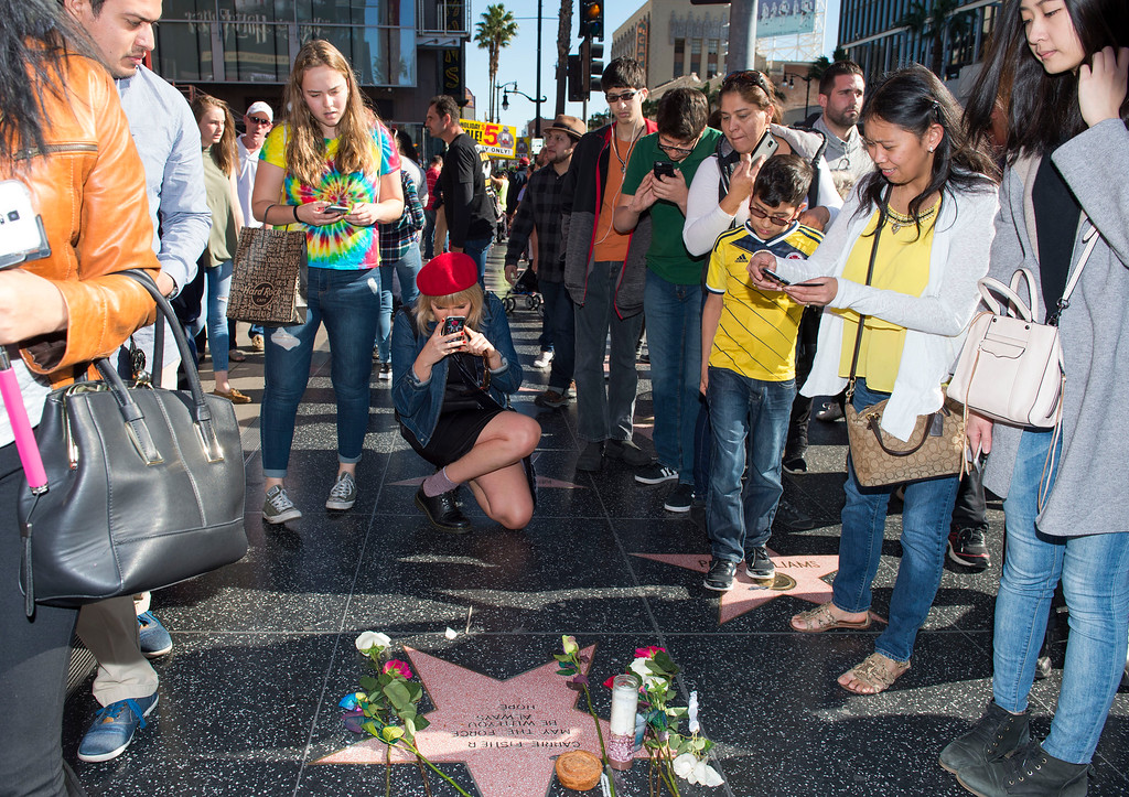 ". People stop by a temporary star made by fans in tribute to actress Carrie Fisher on Hollywood Walk of Fame in Hollywood, California, on December 28, 2016. Friends, fans and Hollywood stars added their voices to a torrent of tributes for ""Star Wars\"" actress Carrie Fisher, who died Tuesday at the age of 60 following a heart attack. (VALERIE MACON/AFP/Getty Images)"