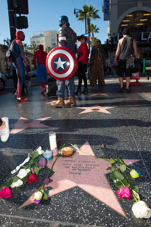 ". People stop by to view a temporary star made by fans in tribute to actress Carrie Fisher on Hollywood Walk of Fame in Hollywood, California, on December 28, 2016. Friends, fans and Hollywood stars added their voices to a torrent of tributes for ""Star Wars\"" actress Carrie Fisher, who died Tuesday at the age of 60 following a heart attack. (VALERIE MACON/AFP/Getty Images)"