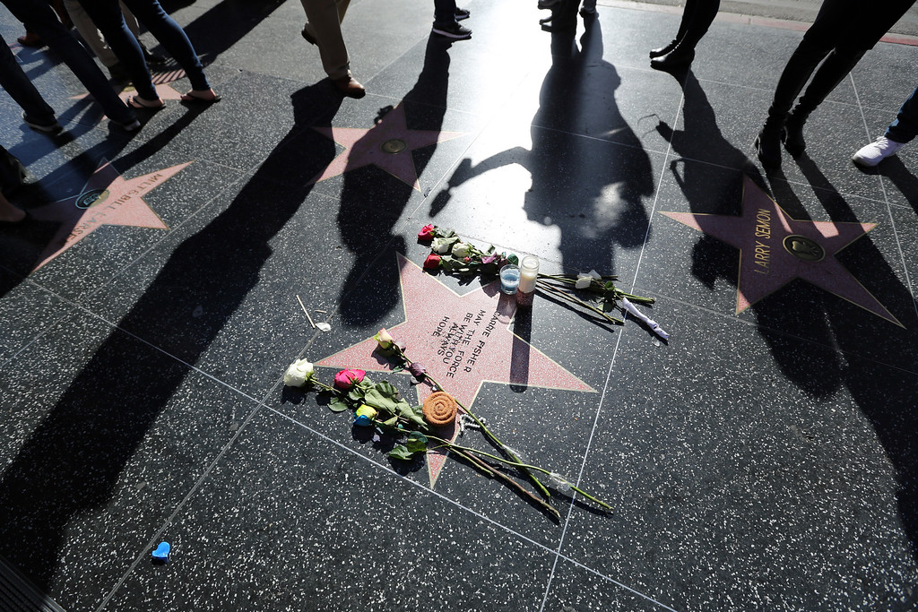 ". An impromptu memorial created on a blank Hollywood Walk of Fame star by fans of late actress and author Carrie Fisher, who does not have an official star on the world-famous promenade, is seen in Los Angeles Wednesday, Dec. 28, 2016. Paste-on letters spell out her name and the phrase ""May the force be with you always. Hope.\"" (AP Photo/Reed Saxon)"