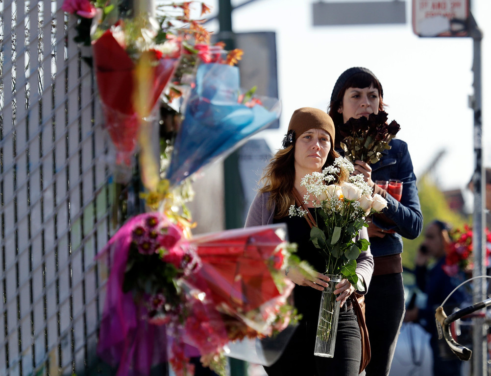 . Well-wishers walk to place flowers at the scene in the aftermath of a warehouse fire, Sunday, Dec. 4, 2016, in Oakland, Calif. Officials said they are continuing to search the charred rubble from the fatal fire that ripped through a late-night dance party in a converted warehouse earlier in the weekend. (AP Photo/Marcio Jose Sanchez)