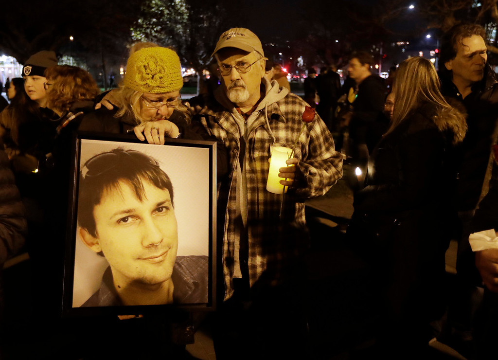 . Judy Hough, left, and her husband Brian, center, hold a picture of their son Travis, who died in a warehouse fire, during a vigil at Lake Merritt on Monday, Dec. 5, 2016, in Oakland, Calif. Family members and friends are being notified as firefighters continue a painstaking search for victims of the Oakland warehouse fire. (AP Photo/Marcio Jose Sanchez)