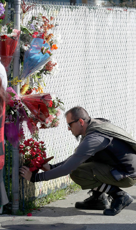 . Flowers are placed at the scene of the aftermath of a warehouse fire, Sunday, Dec. 4, 2016, in Oakland, Calif. Officials said they are continuing to search the charred rubble from the fatal fire that ripped through a late-night dance party in a converted warehouse earlier in the weekend. (AP Photo/Marcio Jose Sanchez)