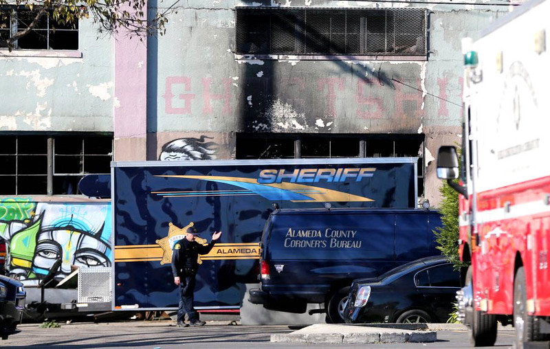. An Alameda County Sheriff\'s officer directs the driver of an Alameda County Coroners Bureau van in front of the structure where at least nine people died in a fire on 31st Avenue in Oakland, Calif., on Saturday, Dec. 3, 2016. (Ray Chavez/Bay Area News Group)