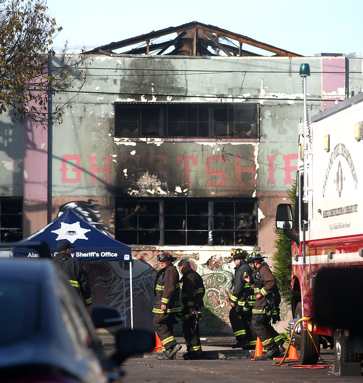 . Firefighters walk along 31st Avenue near International Boulevard on Sunday, Dec. 4, 2016, in Oakland, Calif.  Officials announced 30 victims have been found so far inside a warehouse after a deadly fire on Friday.  (Photo by Aric Crabb/Bay Area News Group)