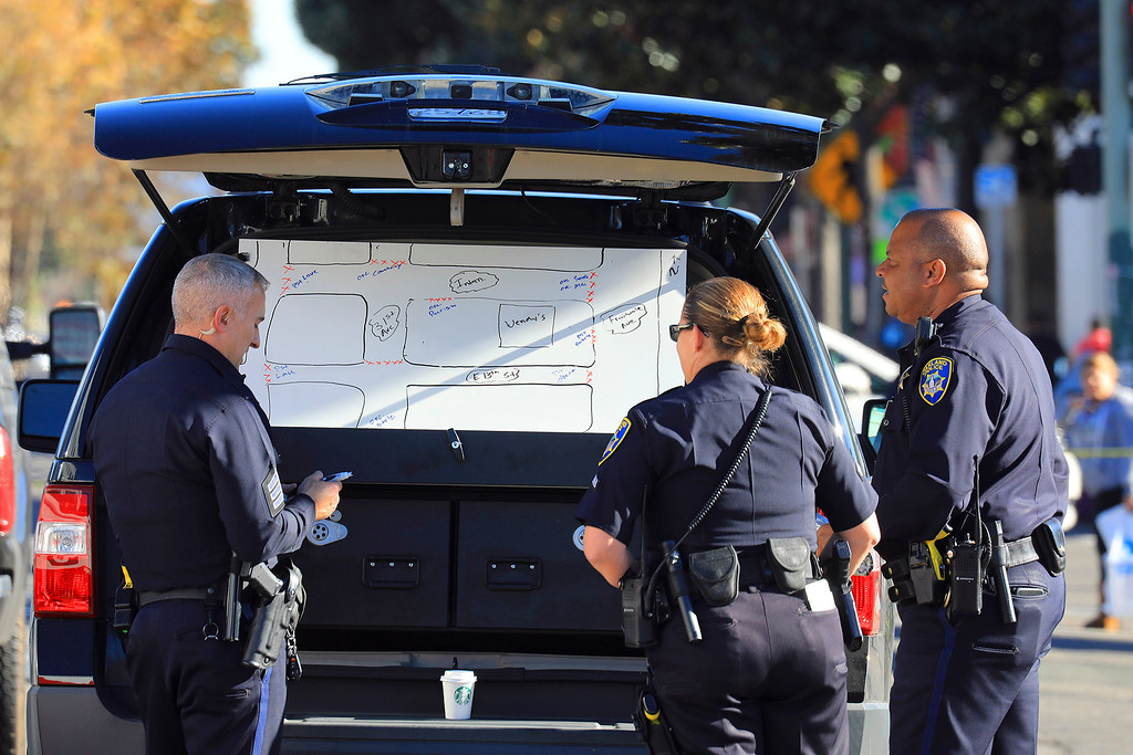 . Police officers review a map of the scene of a fire at a warehouse in Oakland, Calif., Dec. 3, 2016. Firefighters picking through the ruins of the warehouse found 15 more bodies overnight Saturday, bringing to 24 the death toll from a fire that ripped through a makeshift nightclub on Friday. (Jim Wilson/The New York Times)