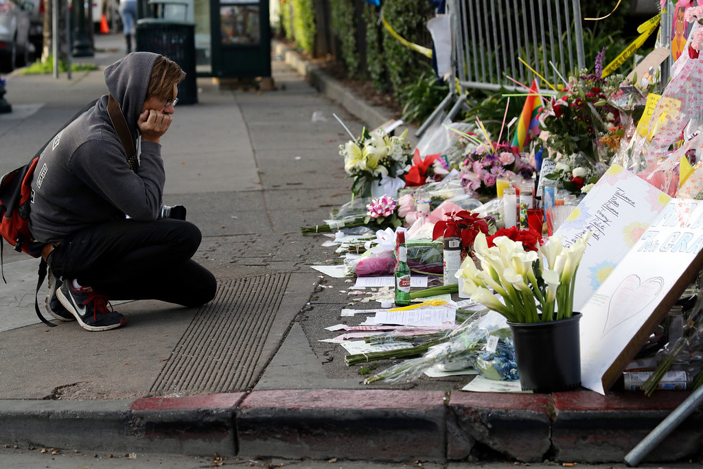 . Nathan Weyland kneels in front of a makeshift memorial at the site of a warehouse fire Tuesday, Dec. 6, 2016, in Oakland, Calif. (AP Photo/Marcio Jose Sanchez)