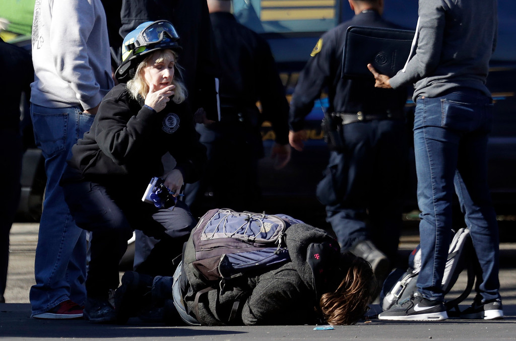 . A unidentified man falls to the ground after speaking to authorities outside of a warehouse destroyed by a fire Saturday, Dec. 3, 2016, in Oakland, Calif. A deadly fire broke out during a rave at a converted warehouse in the San Francisco Bay Area. (AP Photo/Marcio Jose Sanchez)
