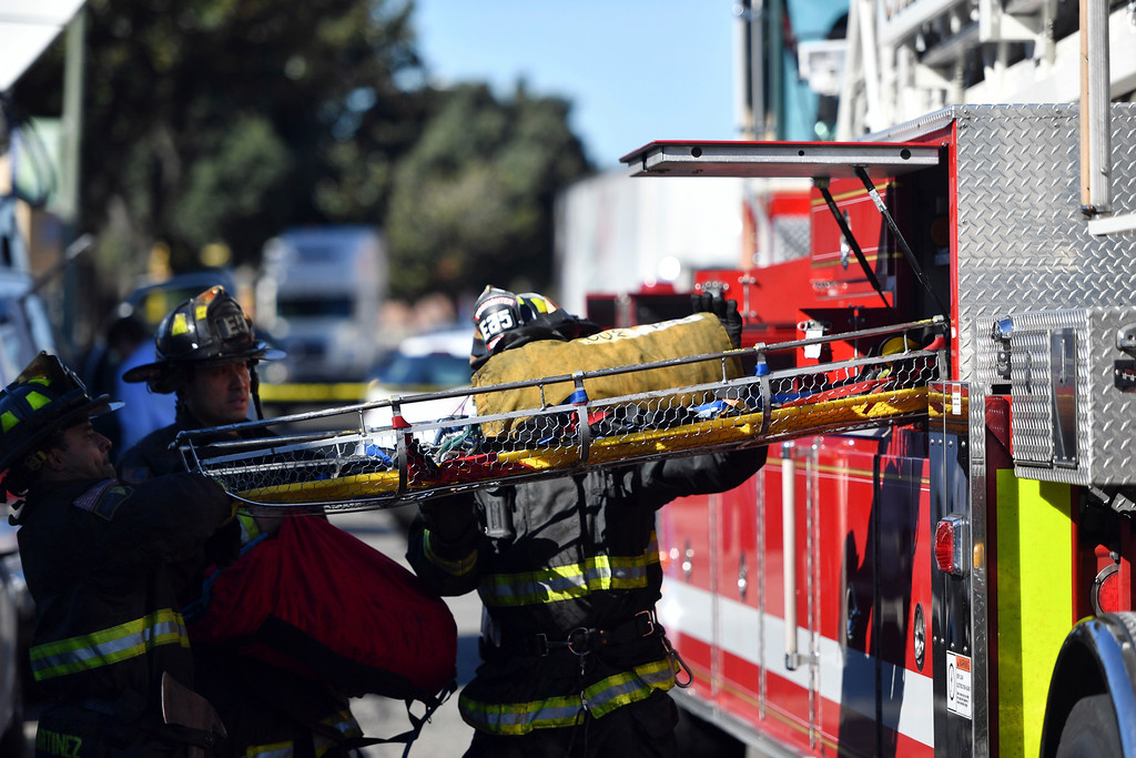 . A stretcher is taken out of a fire truck at the scene of a fire that destroyed a warehouse Saturday, Dec. 3, 2016, in Oakland, Calif. A deadly fire broke out during a rave at the converted warehouse in the San Francisco Bay Area. (AP Photo/Josh Edelson)
