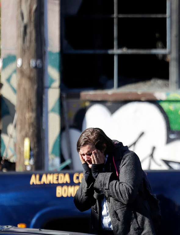 . A unidentified man covers his face outside of a warehouse destroyed by a fire Saturday, Dec. 3, 2016, in Oakland, Calif. A deadly fire broke out during a rave at the converted warehouse in the San Francisco Bay Area. (AP Photo/Marcio Jose Sanchez)