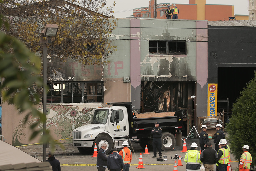 . OAKLAND, CA - DECEMBER 05: Law enforcement and firefighters are seen at the site of a warehouse fire that has claimed the lives of at least thirty-six people on December 5, 2016 in Oakland, California. The fire took place during a musical event late Friday night. (Photo by Elijah Nouvelage/Getty Images)