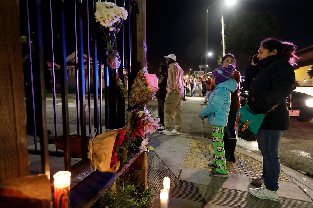 . Flowers and candles are placed at the site of a warehouse fire Saturday, Dec. 3, 2016, in Oakland, Calif. Firefighters struggled to get to bodies in the rubble Saturday, after a deadly fire tore through a converted Oakland warehouse during a late-night electronic music party Friday, making the charred structure unsafe for emergency crews to enter. (AP Photo/Marcio Jose Sanchez)