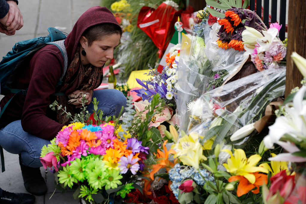 . A woman places flowers at a makeshift memorial at the site of a warehouse fire Tuesday, Dec. 6, 2016, in Oakland, Calif. (AP Photo/Marcio Jose Sanchez)
