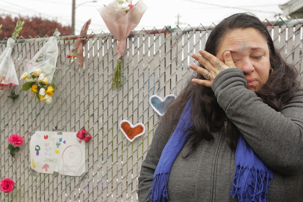 . OAKLAND, CA - DECEMBER 05: Danielle Boudreaux, who knew the man who rented out the Ghost Ship warehouse for parties and was a frequent visitor herself, cries by a makeshift memorial near the site of a warehouse fire that has claimed the lives of at least thirty-six people on December 5, 2016 in Oakland, California. The fire took place during a musical event late Friday night. (Photo by Elijah Nouvelage/Getty Images)