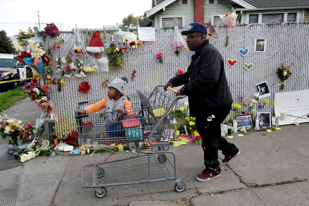 . Robert Lewis, right, and his daughter Sophie walk past a makeshift memorial in memory of victims of a warehouse fire near the site Monday, Dec. 5, 2016, in Oakland, Calif. The death toll in the Oakland warehouse fire climbed Monday with more bodies still feared buried in the blackened ruins, and families anxiously awaited word of their missing loved ones. (AP Photo/Marcio Jose Sanchez)