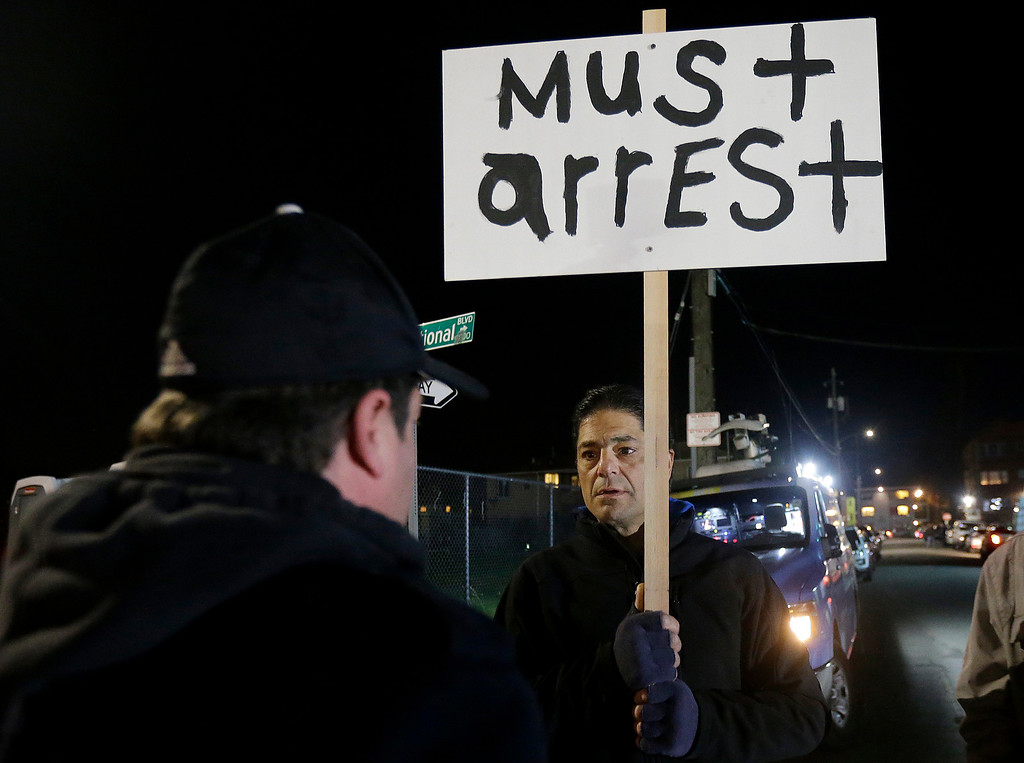 . Tom Dispenza holds up a sign about the manager of a warehouse that caught fire in Oakland, Calif., Tuesday, Dec. 6, 2016. The fire erupted Friday, Dec. 2, killing dozens. (AP Photo/Jeff Chiu)
