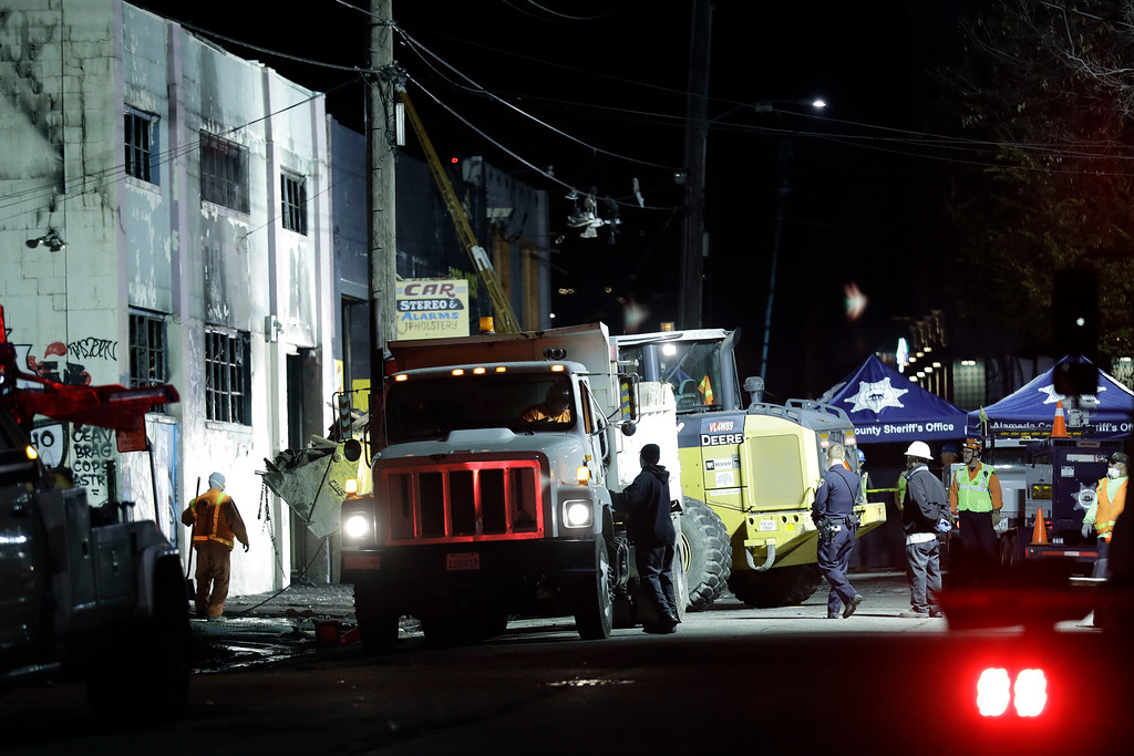 . Emergency crews perform clean up in the aftermath of a warehouse fire Saturday, Dec. 3, 2016, in Oakland, Calif. Firefighters struggled to get to bodies in the rubble Saturday, after a deadly fire tore through a converted Oakland warehouse during a late-night electronic music party Friday, making the charred structure unsafe for emergency crews to enter. (AP Photo/Marcio Jose Sanchez)