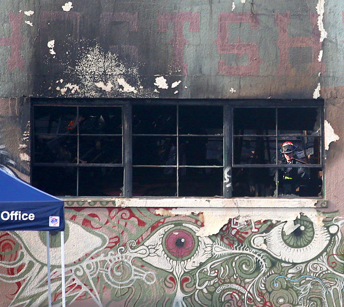 . A firefighter is seen through broken windows of a warehouse along 31st Avenue near International Boulevard on Sunday, Dec. 4, 2016, in Oakland, Calif.  Officials announced 30 victims have been found so far inside a warehouse after a deadly fire broke out on Friday. (Photo by Aric Crabb/Bay Area News Group)