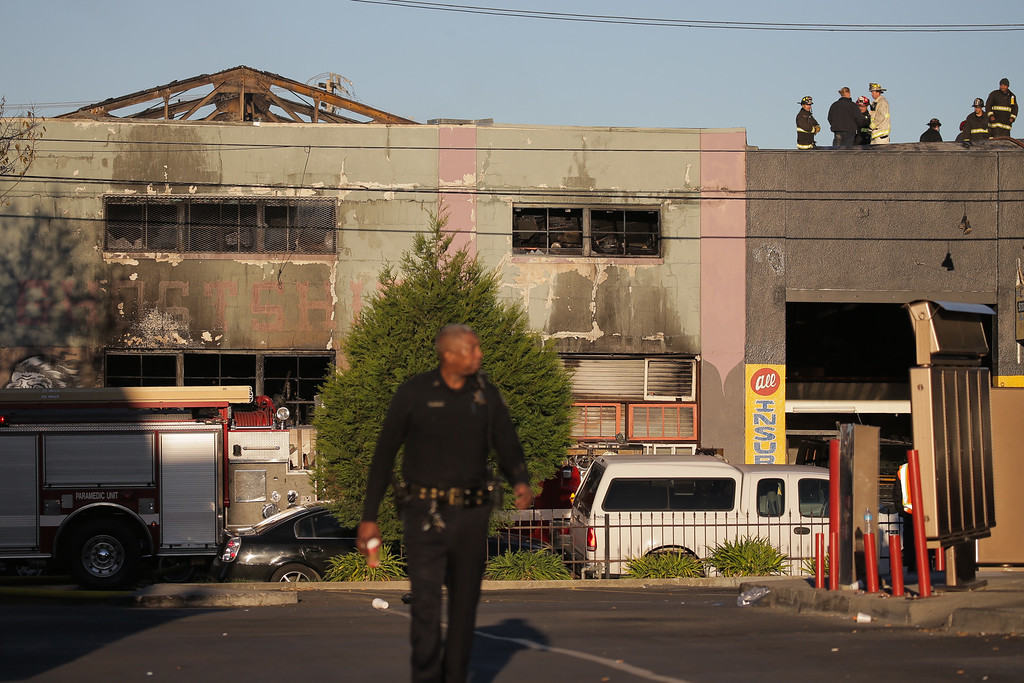 . OAKLAND, CA - DECEMBER 03:  Firefighters and police at the scene of a overnight fire that claimed the lives of at least nine people at a warehouse in the Fruitvale neighborhood on December 3, 2016 in Oakland, California. The warehouse was hosting an electronic music party.  (Photo by Elijah Nouvelage/Getty Images)