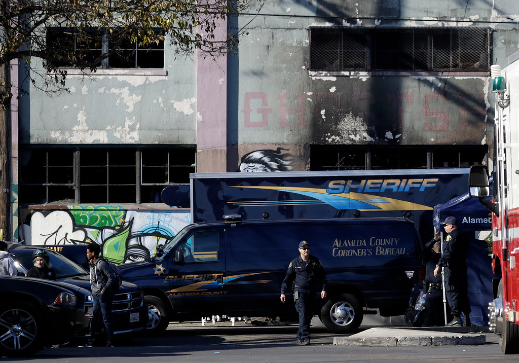 . A coroner\'s van is parked outside of a warehouse after it was destroyed by a fire Saturday, Dec. 3, 2016, in Oakland, Calif.  Oakland fire chief Teresa Deloche-Reed said many people were unaccounted for as of Saturday morning and authorities were working to verify who was in the cluttered warehouse when the fire broke out around 11:30 p.m. Friday.  (AP Photo/Marcio Jose Sanchez)
