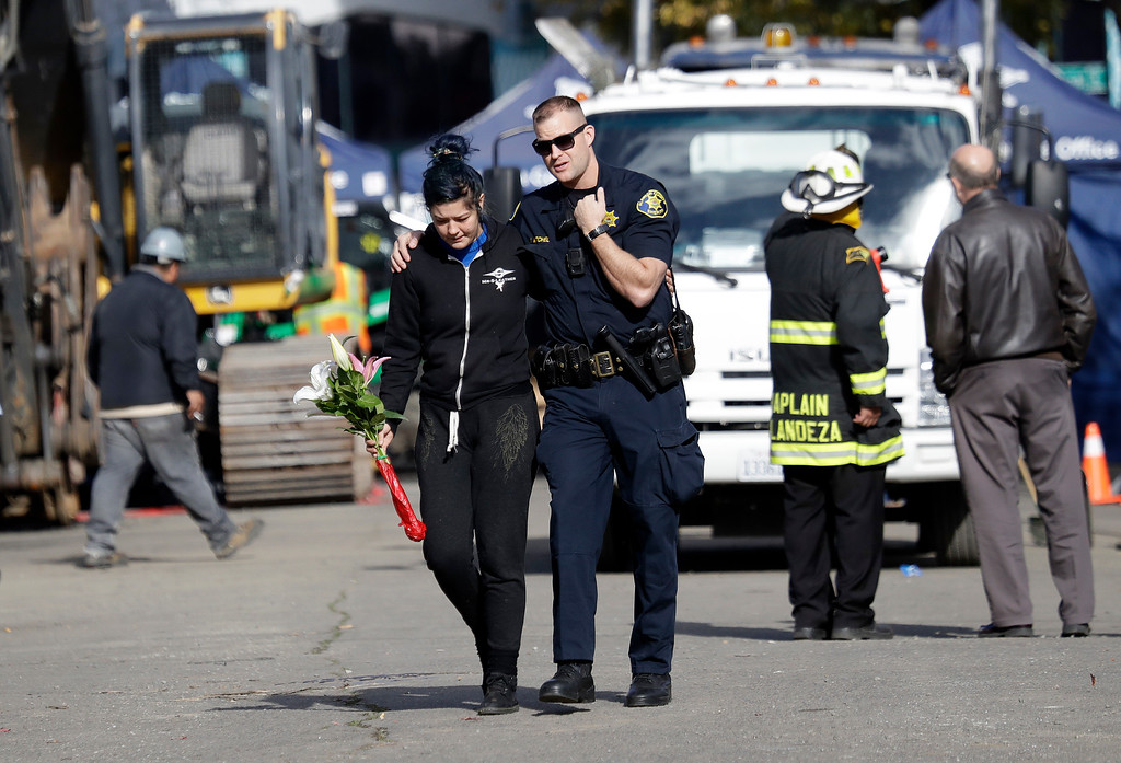 . An Alameda County Sheriff, center, escorts a woman carrying flowers at the site of a warehouse fire Tuesday, Dec. 6, 2016, in Oakland, Calif. (AP Photo/Marcio Jose Sanchez)