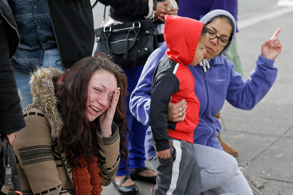 . Hillary Morse, left, cries as Eva Ramirez, right, talks with her four-year-old grandson, Jacob Ramirez, while viewing a makeshift memorial near the site of a warehouse fire Wednesday, Dec. 7, 2016, in Oakland, Calif. Recovery efforts at the Oakland warehouse fire have ended officials said Wednesday. Morse lost two of her friends in the fire and had planned to visit the warehouse the night it happened. (AP Photo/Eric Risberg)