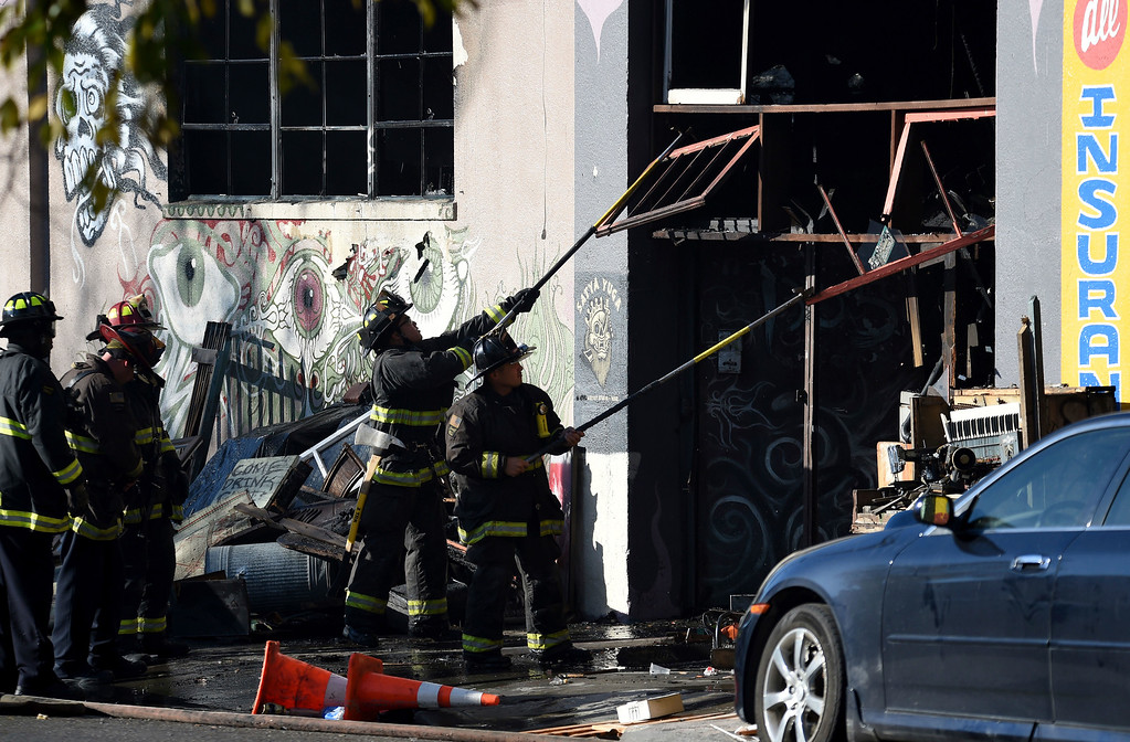 . Firefighters clear an entry to a smoldering building after a fire tore through a warehouse party early Saturday, Dec. 3, 2016 in Oakland.   Oakland fire chief Teresa Deloche-Reed said many people were unaccounted for as of Saturday morning and authorities were working to verify who was in the cluttered warehouse when the fire broke out around 11:30 p.m. Friday. (AP Photo/Josh Edelson)