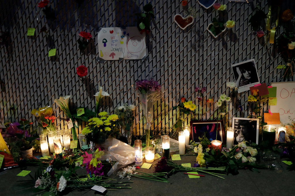 . Candles, photos and flowers are place at a makeshift memorial near the site of a warehouse fire Monday, Dec. 5, 2016, in Oakland, Calif. The death toll in the fire climbed Monday with more bodies still feared buried in the blackened ruins, and families anxiously awaited word of their missing loved ones. (AP Photo/Marcio Jose Sanchez)