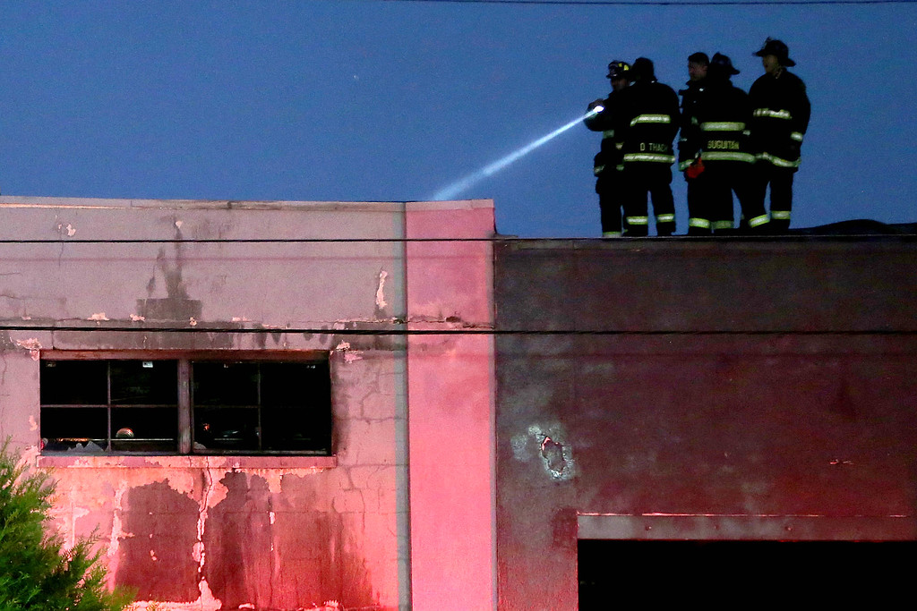 . December 3, 2016 - Oakland, California, U.S. - Firefighters survey a fatal fire where at least nine people died in a warehouse party on 31st Avenue in Oakland. (Credit Image: © Ray Chavez/TNS via ZUMA Wire)