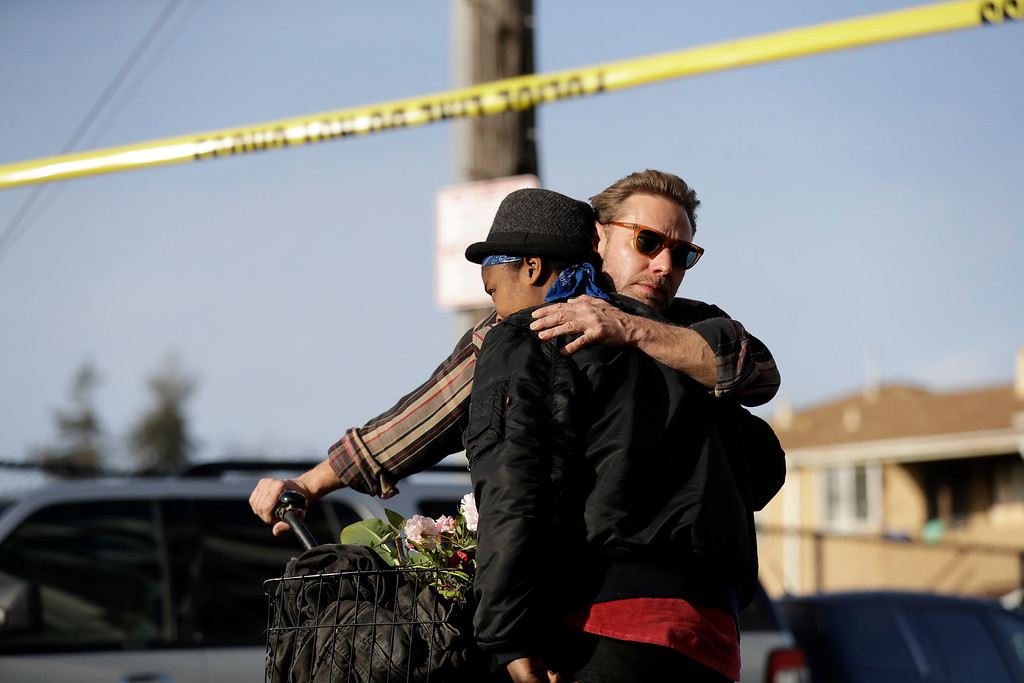 . People embrace at the scene of a warehouse fire Sunday, Dec. 4, 2016, in Oakland, Calif. Officials in Oakland say the dozens of people confirmed dead in a fire at a warehouse range in age from teenagers to 30-plus years old.(AP Photo/Marcio Jose Sanchez)