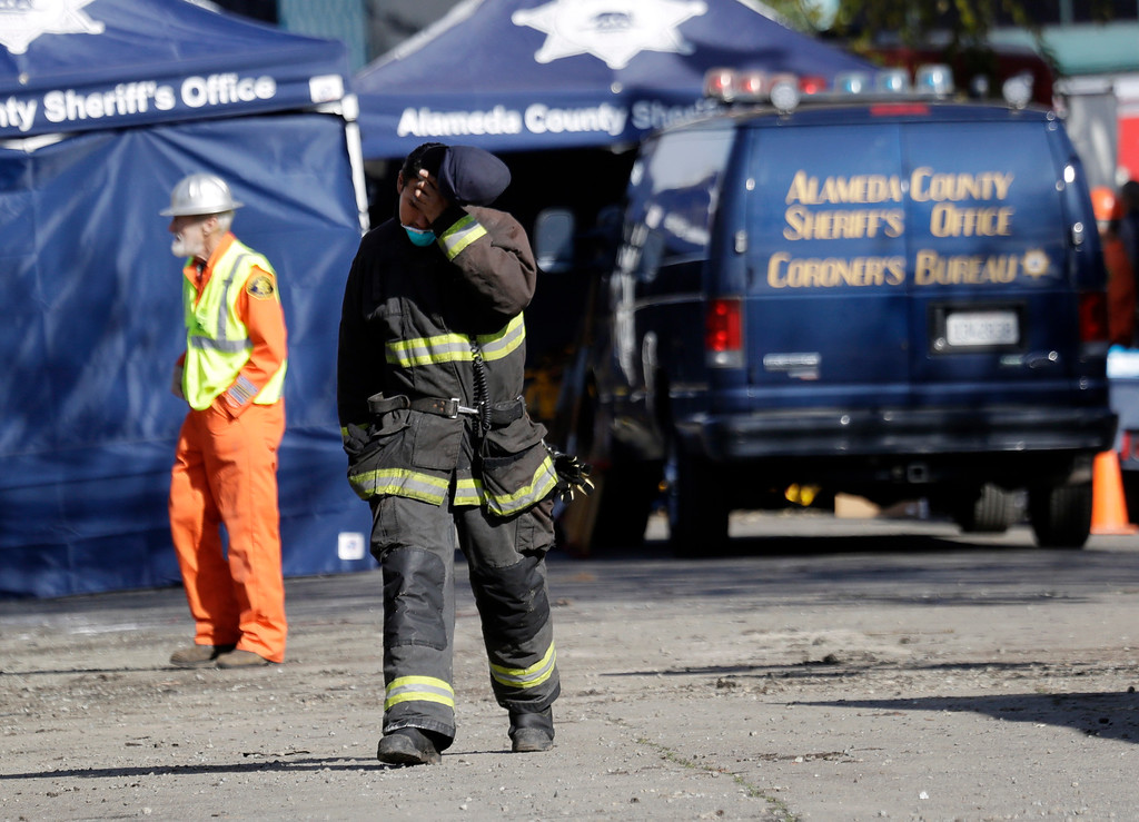 . A firefighter walks at the site of a warehouse fire, Sunday, Dec. 4, 2016, in Oakland, Calif. Officials said they are continuing to search the charred rubble from the fatal fire that ripped through a late-night dance party in a converted warehouse earlier in the weekend. (AP Photo/Marcio Jose Sanchez)