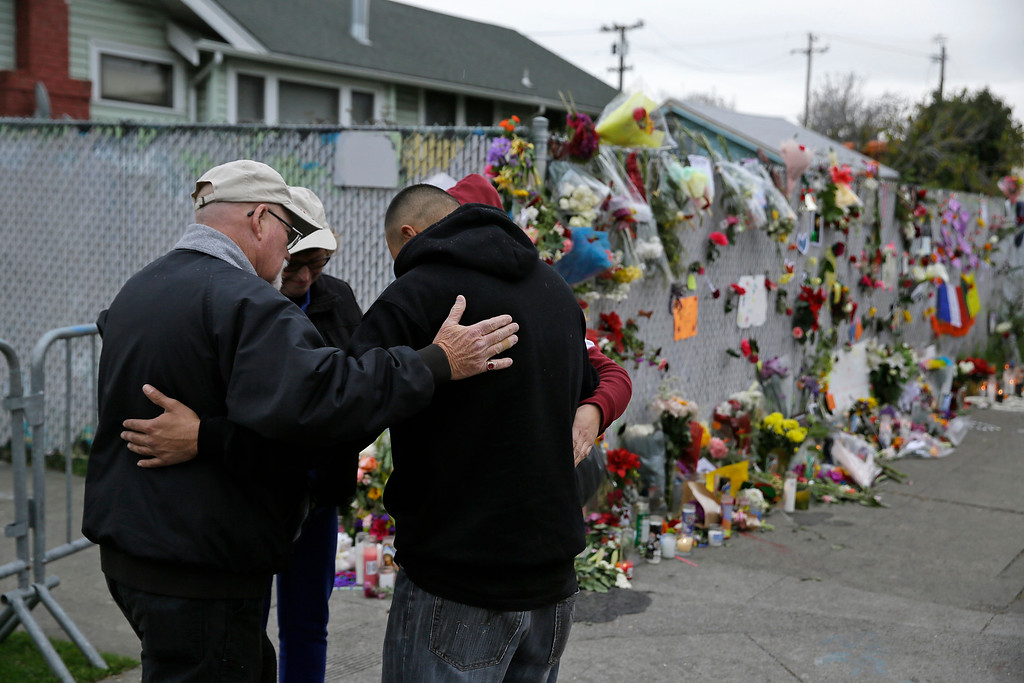 . John Gaut, left, with the Billy Graham Rapid Response Team, leads a group in prayer near the site of a warehouse fire Wednesday, Dec. 7, 2016, in Oakland, Calif. The fire that killed over two dozen people during a dance party at an Oakland warehouse grew rapidly and was raging by the time people on the second floor of the building detected it, trapping them upstairs, investigators said. (AP Photo/Eric Risberg)